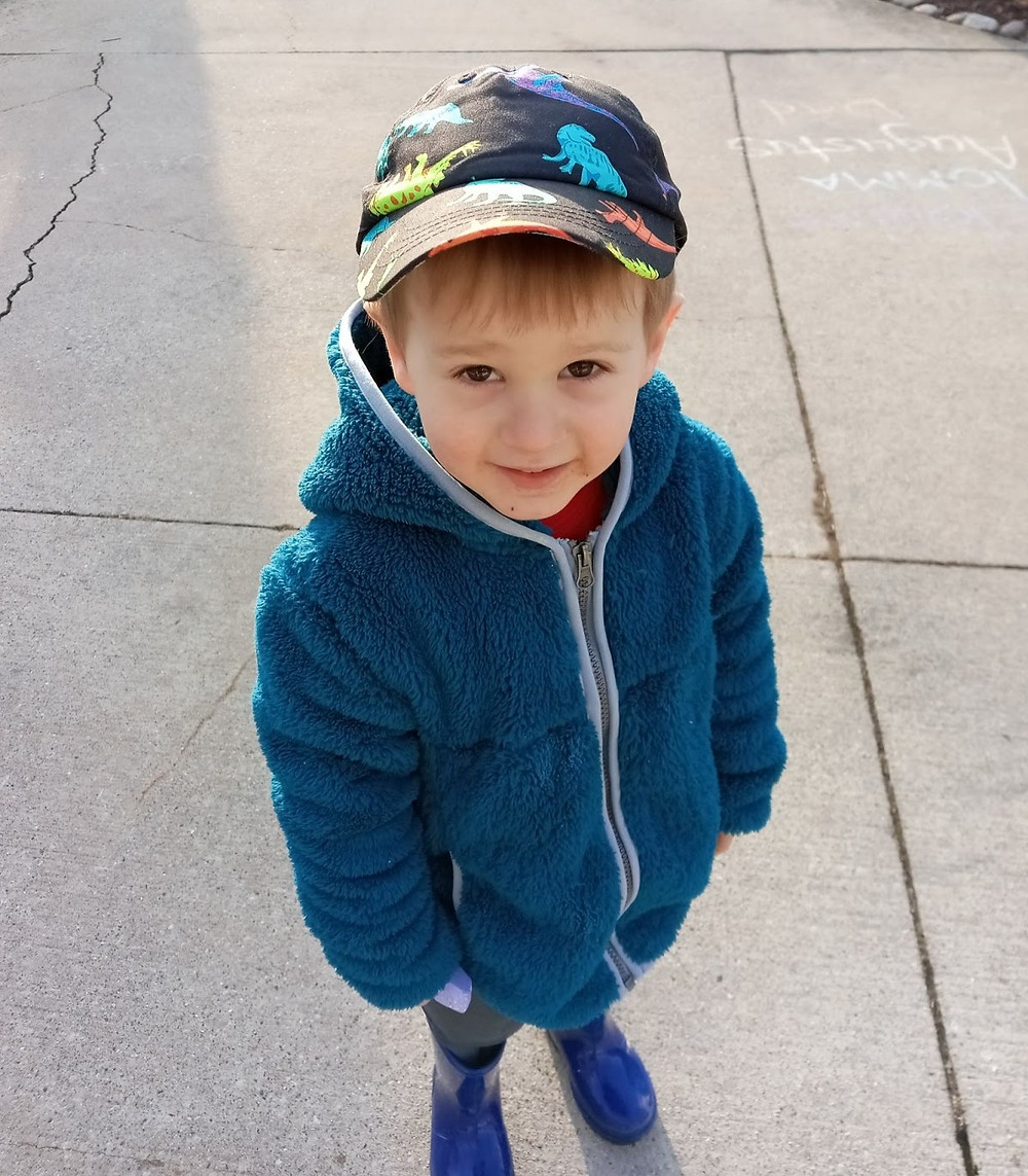 little-boy-in-blue-coat-smiles-at-camera