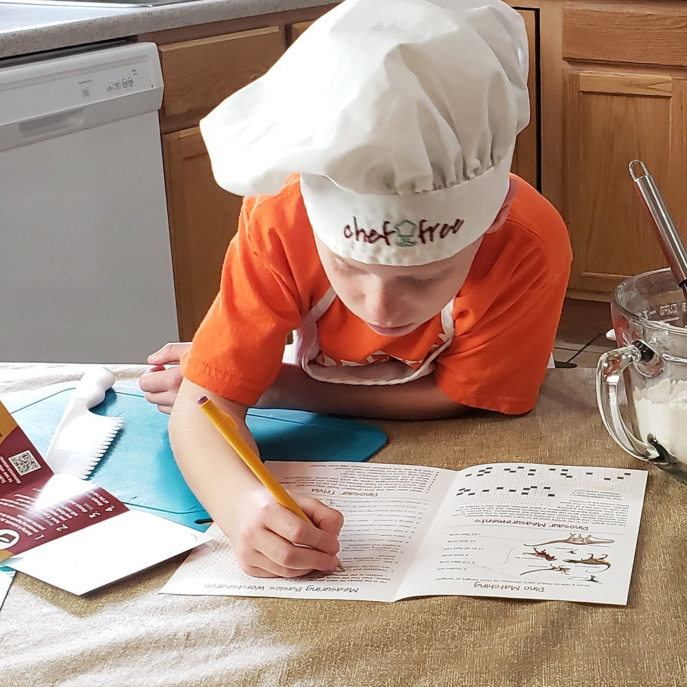 little-boy-with-chef-hat-writing-on-paper-at-kitchen-table