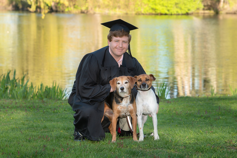 graduate-with-two-dogs-in-front-of-lake