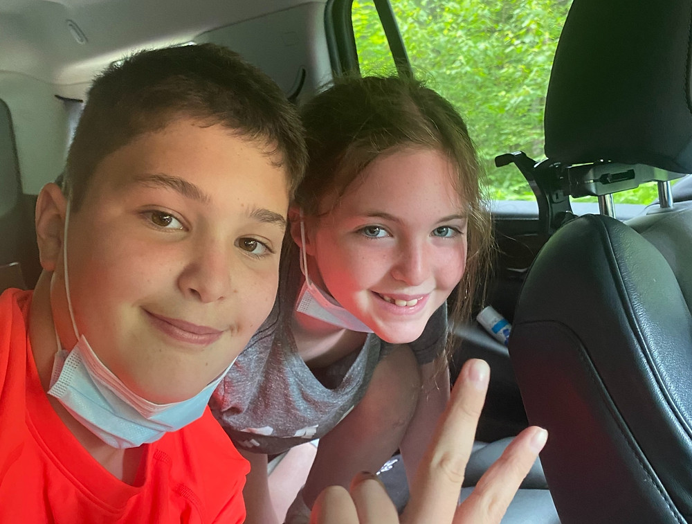 two-kids-with-smiles-ride-in-backseat-of-car