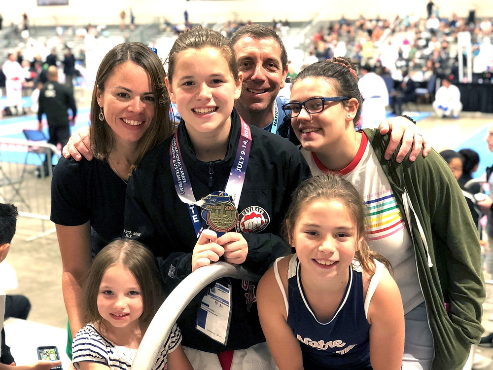 family-of-five-smiles-at-camera-after-daughter-wins-karate-national-championship