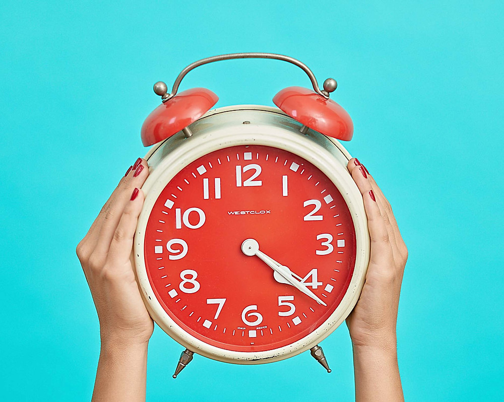 large-white-alarm-clock-with-orange-face-held-up-by-two-hands-against-turquoise-background