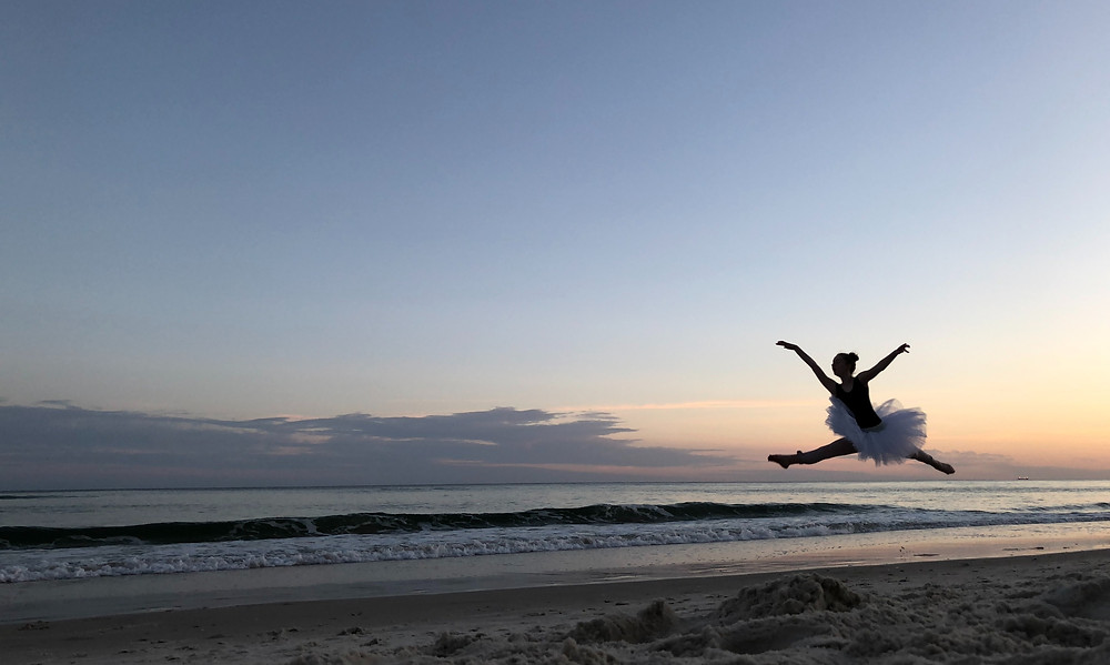 ballerina-leaping-into-air-on-beach-at-sunset