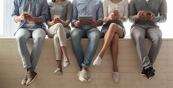 young-adults-sitting-next-to-eachother-with-iPhones