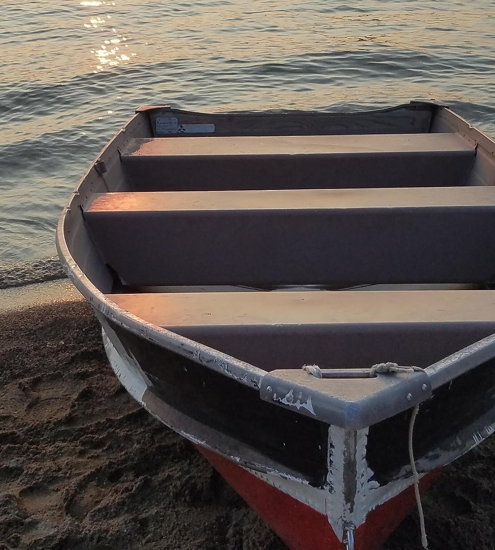 rowboat-on-beach-near-water