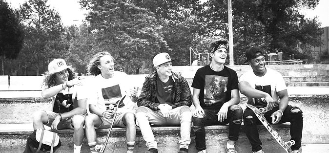 teenage-boys-sitting-on-wall-with-skateboards