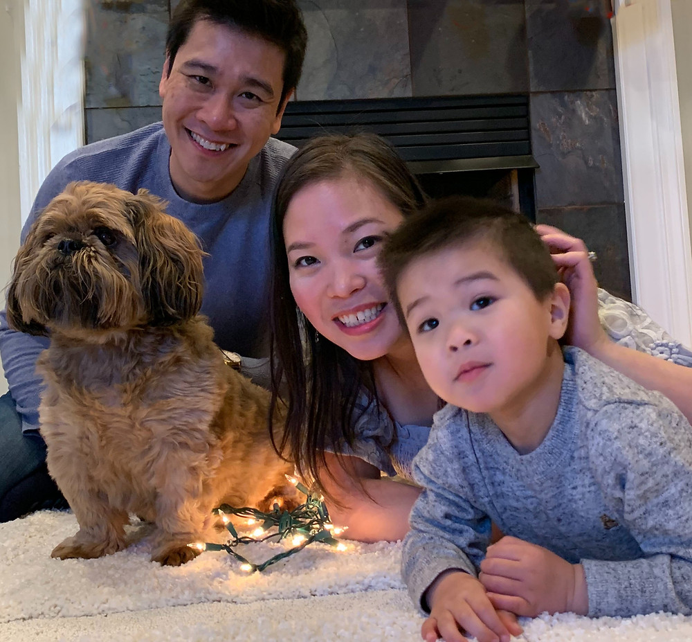 family-of-three-with-dog-in-front-of-fireplace-hung-with-Christmas-stockings