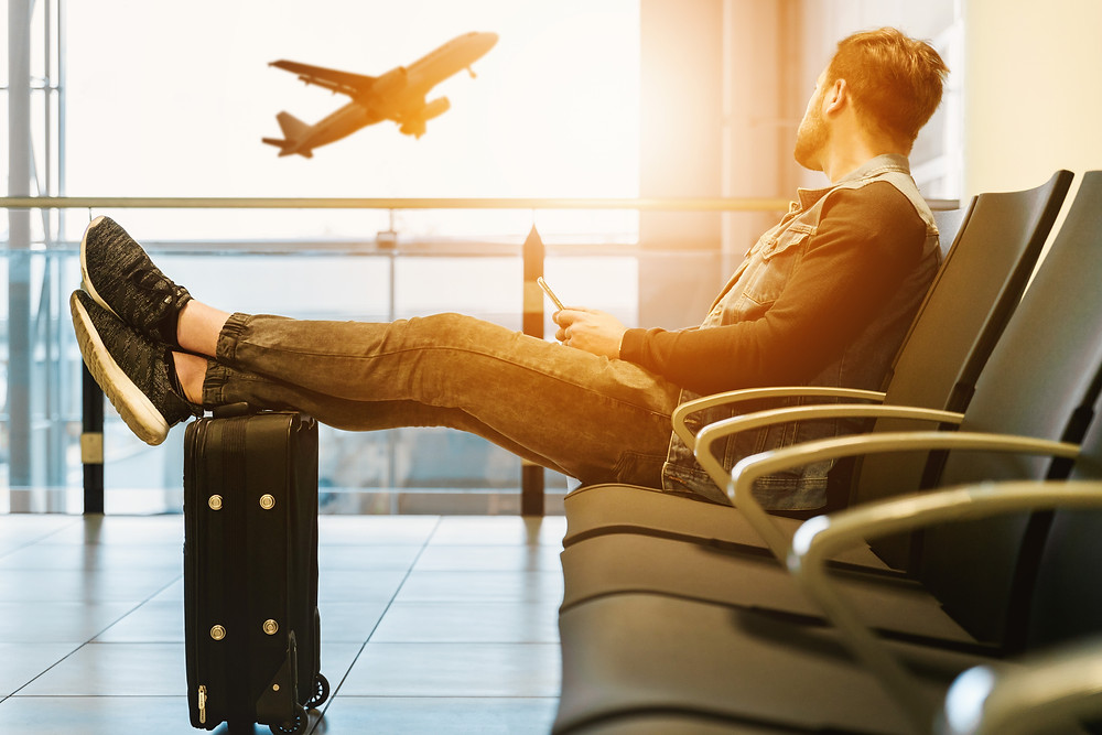 man-with-suitcase-sits-waits-in-airport-for-flight-looks-at-plane-taking-off