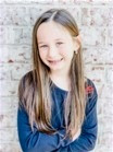little-girl-with-long-hair-smiling-in-front-of-brick-wall