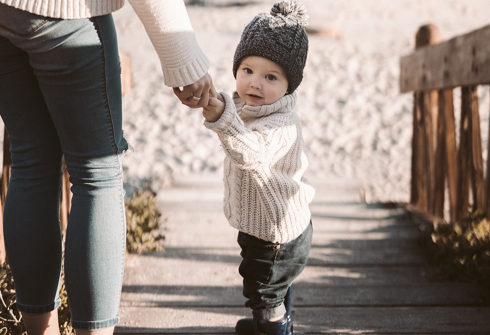 toddler-stands-on-wooden-stairs-that-lead-down-to-sand-holding-mothers-hand