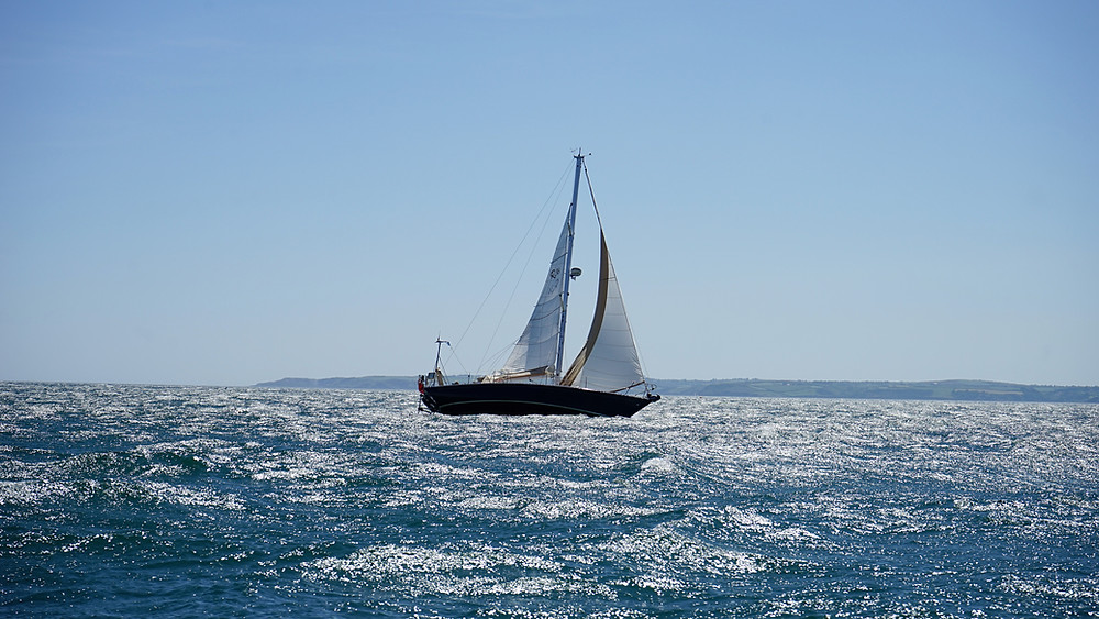 sailboat-under-full-sail-on-blue-ocean-with-blue-sky