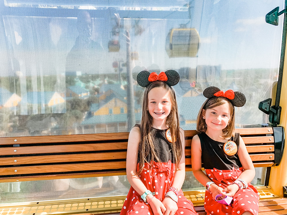 two-girls-sit-on-bench-at-Disney-World-with-Mickey-Mouse-hats