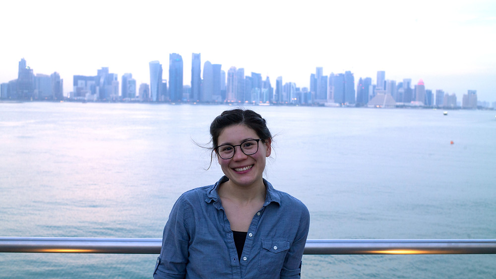young-woman-standing-in-front-of-water-dubai-skyline