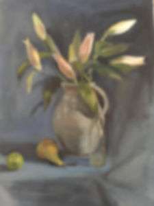 A bunch of Lilies in a jug on a table with a lime, pear and a glass bottle