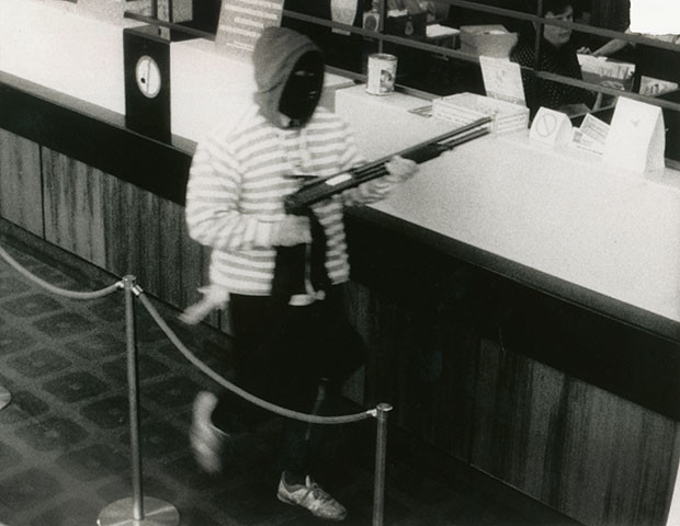 A black-and-white CCTV still image of Christopher Binse carrying a shotgun, wearing a horizontal striped jersey, a dark hoodie pulled over the black balaclava on his head inside a bank, walking left to right between the teller counter and a sash rope barrier