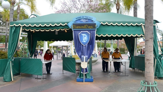 A temporary security checkpoint in a green marquee at Disneyland, Anaheim, manned by three staff one in a red polo shirt, the other two in orange.