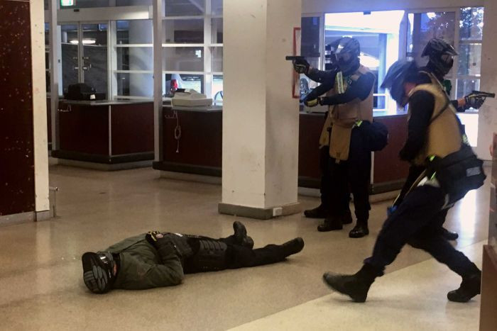 A role-playing actor simulates a casualty by lying on the ground wearing a green flight suit and protective facemask as armed police in blue tactical dress with coyote brown armoured vests and protective masks clear the area