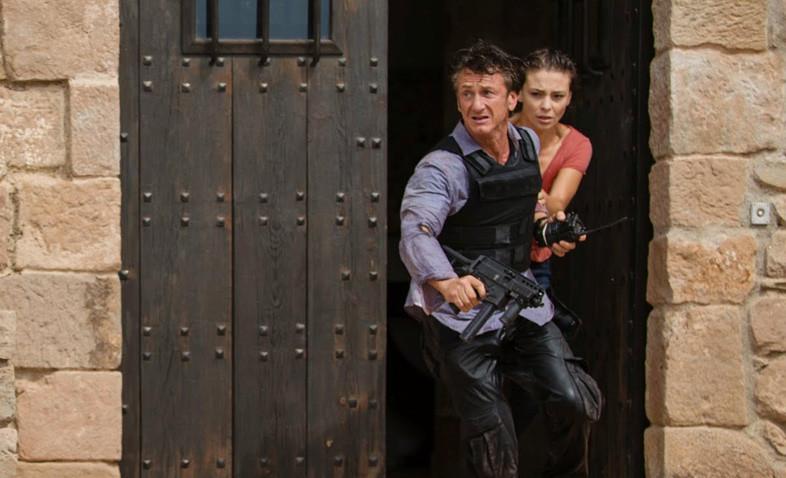 Sean Penn in body armour with radio and sub-machine gun and Jasmine Trinca in The Gunman