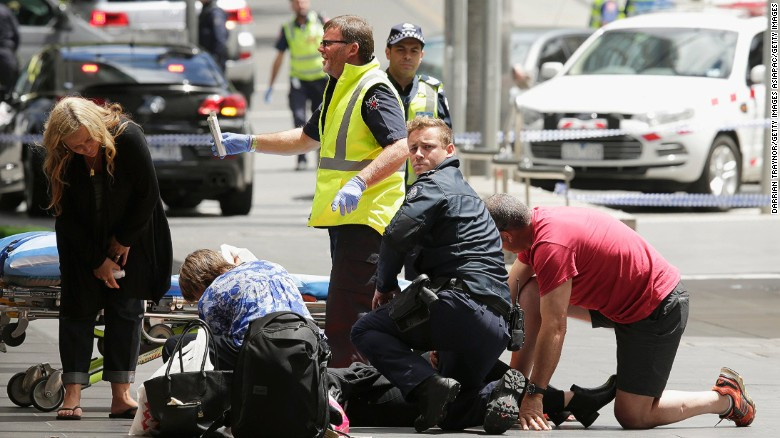 Victoria Police officers and an Ambulance Victoria paramedic provide first aid to victims of the Bourke Street vehicle rampage. Two women assist in providing first aid in front of a stretcher