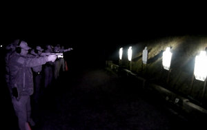 A line of people with handguns an flashlights practice shooting at targets seven metres away at night that are illuminated by the individual flashlights