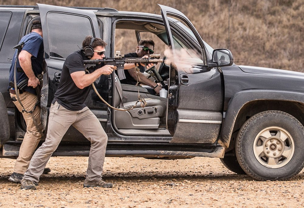 A group of four United States Marine Corps Special Operators with rifles firing on a range practicing from a SUV