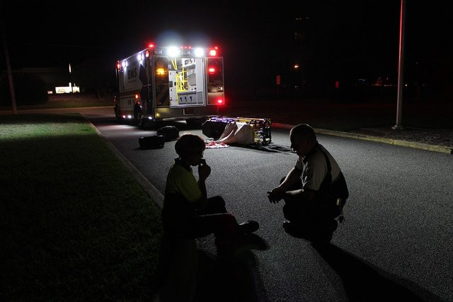 A paramedic comforts a person on a nighttime street while an ambulance with a knocked over gurney sits under lights in the background