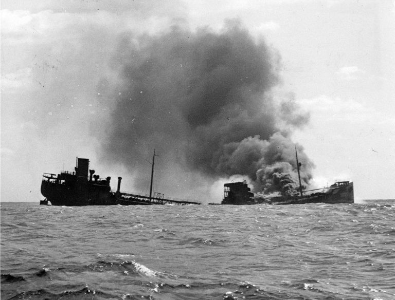 A black-and-white image of a tanker ship hit by a torpedo burns as it sinks beneath the north atlantic sea
