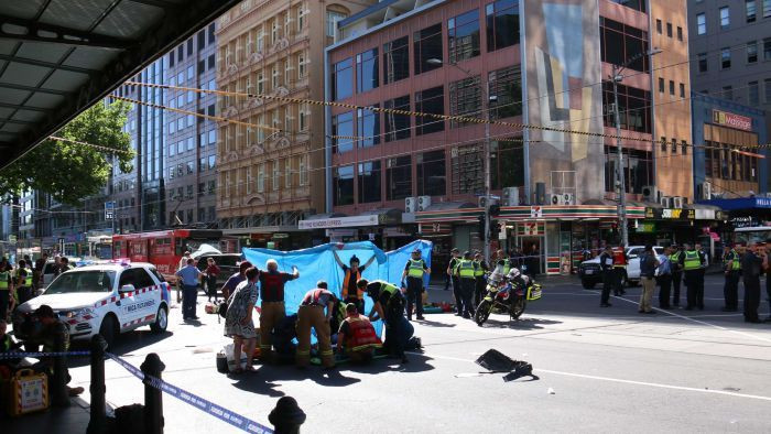 Police and Ambulance responders screen a casualty with a blue tarp in the aftermath of the December 2017 Melbourne vehicle attack in front of a MICA unit