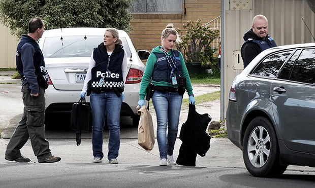 Two female detectives wearing POLICE vests over plain clothes - both in jeans, the leading detective in a green long sleeve top, the following in a white long sleeve top carry evidence including a brown paper bag, a set of body-armour and weapons walk past two male colleagues between a white Ford Falcon sedan and a gunmetal Holden Commodore station wagon