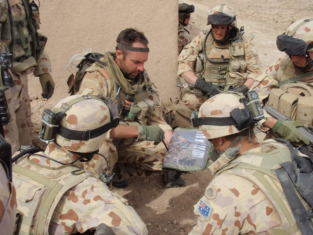"A 2RAR (Australian Army) section commander issues orders to his section during a patrol in Afghanistan in 2008. All wear early 2000s Australian Disruptive Pattern Desert Uniform (""Desert Cams"")"