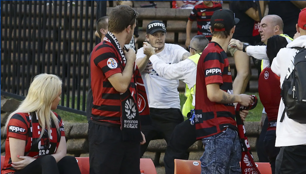 Two male Western Sydney Wanderers fans in red and black striped replica jerseys stand while a female fan, also in a WSW replica jersy sits and watch contracted security guards in white shirts and yellow hi-vis vests scuffle with another fan in a white shirt and black baseball cap emblazoned with the word SYDNEY