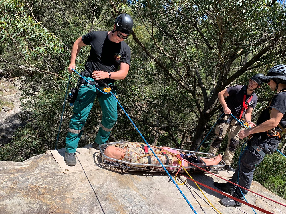 A man in green working trousers and a black t-shirt with a black safety helmet prepares to abseil from a rock in the foreground while on the other side of a dummy casualty in disruptive pattern desert uniform laid in an extraction cage another man in black t-shirt and helmet with tan work trousers also prepares to abseil. A third man in blue work trousers, black t-shirt and green helmet prepares to belay the casualty