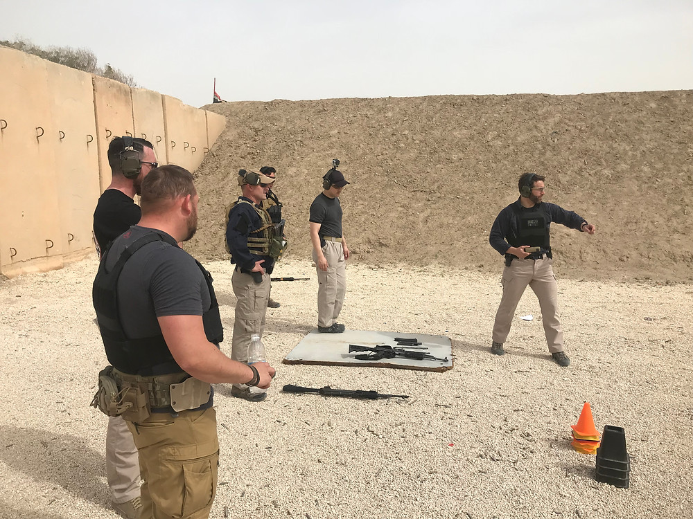 Five security contractors in personal body armour, blue shirts and cargo pants stand in a line with firearms AK-47 and M21 laid on the ground to receive instruction from a trainer dressed similarly who gestures downrange at a training area in Baghdad, Iraq
