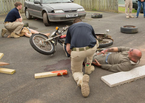 At a simulated Motor Vehicle Accident a man lies next to a motorcycle while a student kneels to practice first aid. In the background, next to a small car, another student kneels to practice on a dummy.