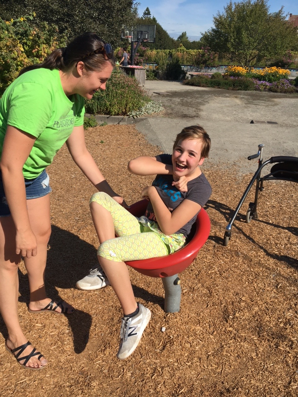 A teen plays in a playground spinner with the help of a summer camp counselor
