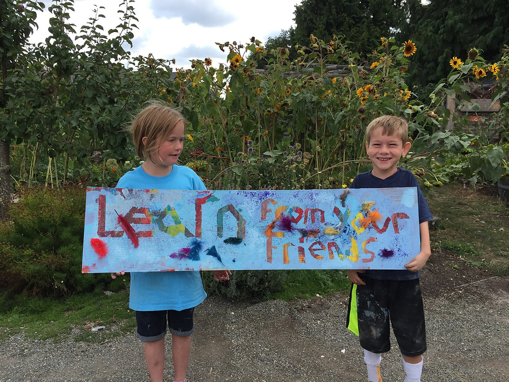 """Two kids hold up a hand painted sign that says """"""""Learn from your friends"""""""