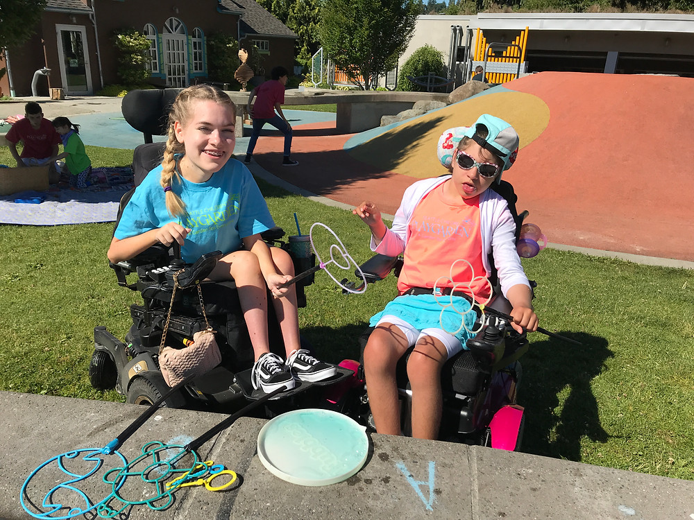 Annie, a summer camp counselor at the PlayGarden drives her power wheelchair to play bubbles with a camper who also uses a power wheelchair.