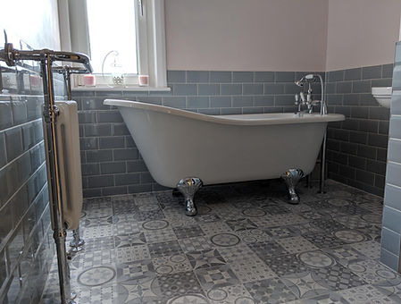 traditional slipper bath on random tile floor