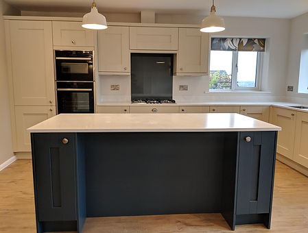 Shaker style kitchen with dark blue island, solid surface worktops and amtico flooring
