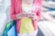 Mulher olhando o SMS no celular, enquanto segura sacolas das compras que fez - serviço de sms da tellegroup