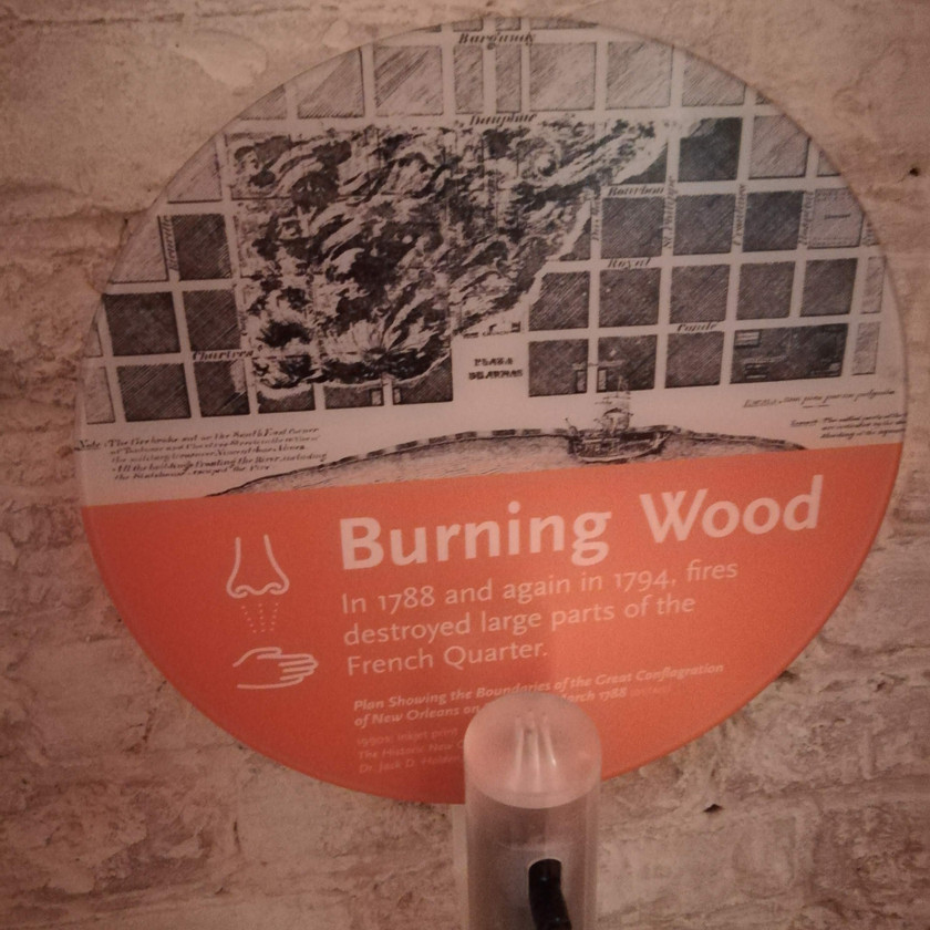 "circle exhibit label with grid map image and title ""burning wood"" scent bottle underneath"
