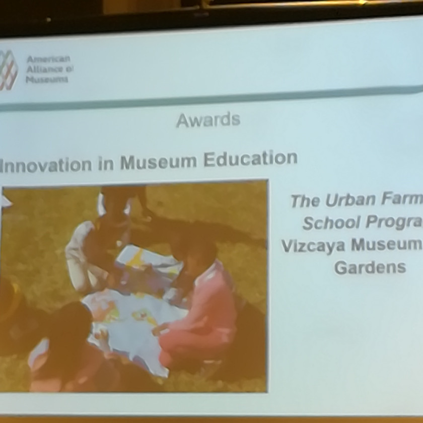 "AAM slide reads ""Awards: Innovation in Museum Education"" with miage of three people sitting on ground around large piece of paper."