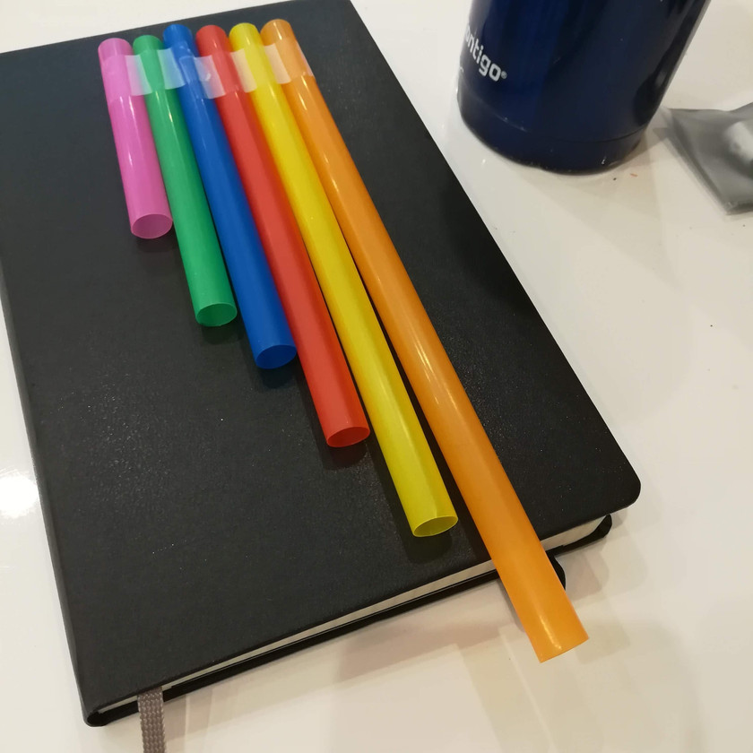 Multicolored jumbo straw taped together to form pan pipes on black notebook