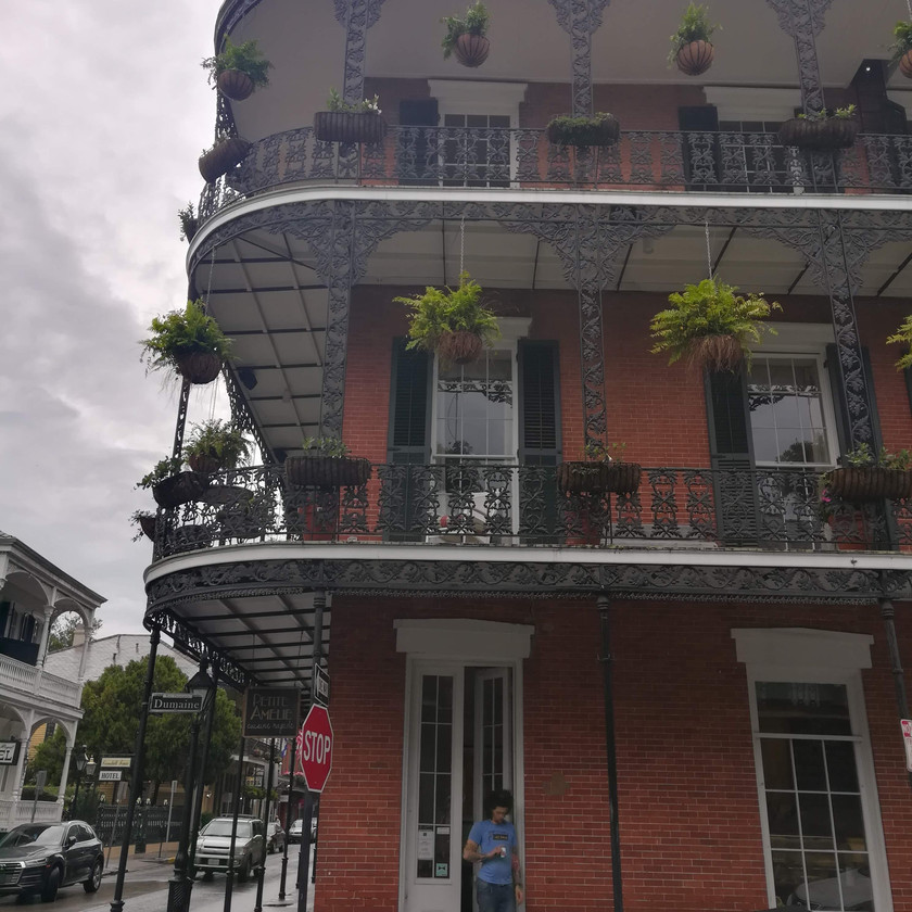 Historic New Orleans brick house with balconies and handing potted plants
