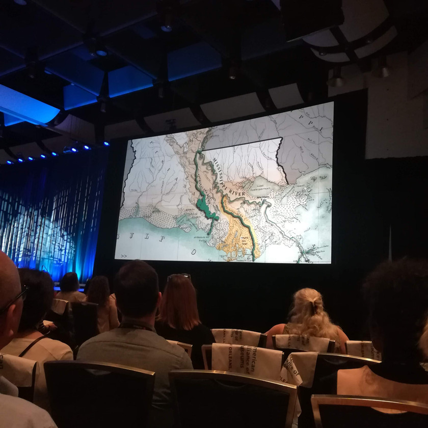 Seated audience looking at map of New Orleans on giant screen