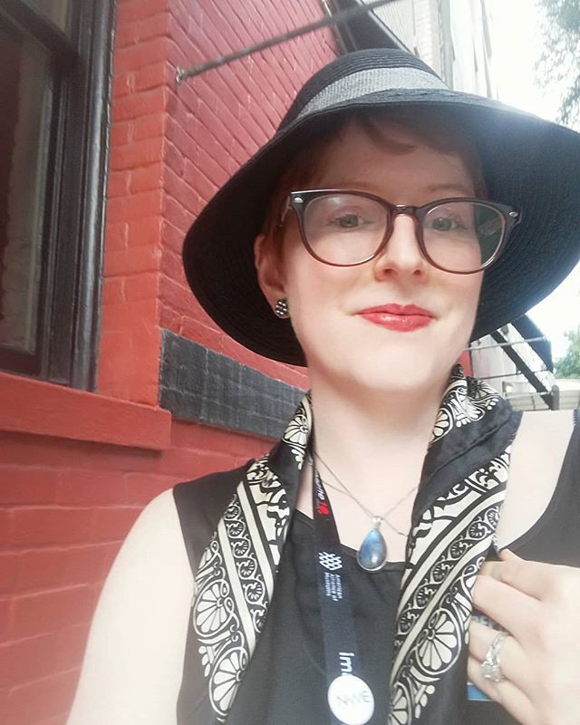 Author standing in front of red brick building in black straw hat, glasses, red lipstick, black and white scarf, and black sleeveless top.