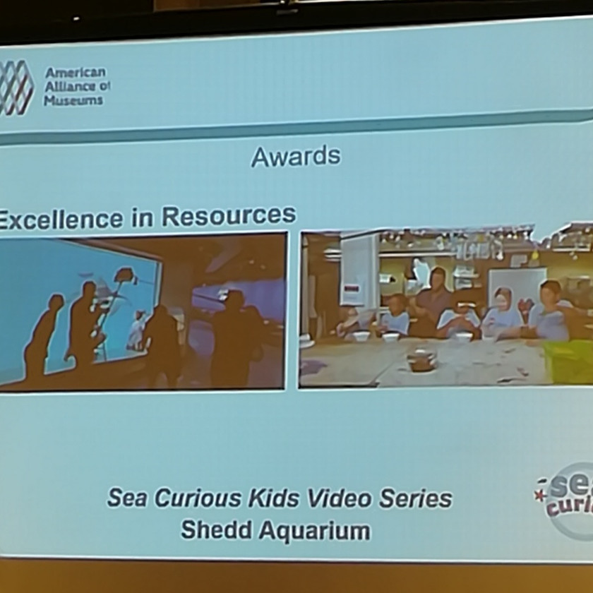 "AAM slide reads ""Awards: Excellence in Resources"" with 2 images. 1 film crew with boom mike in front of aquarium wall. 2: Four children sitting at large table facing camera"