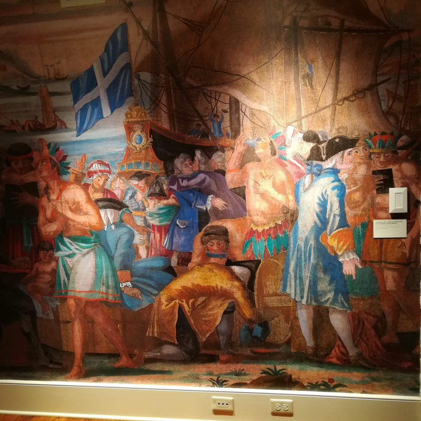 Wall sized reproduction of early painting depicting an early MardiGras celebration with Native Americans and colonizers in New Orleans