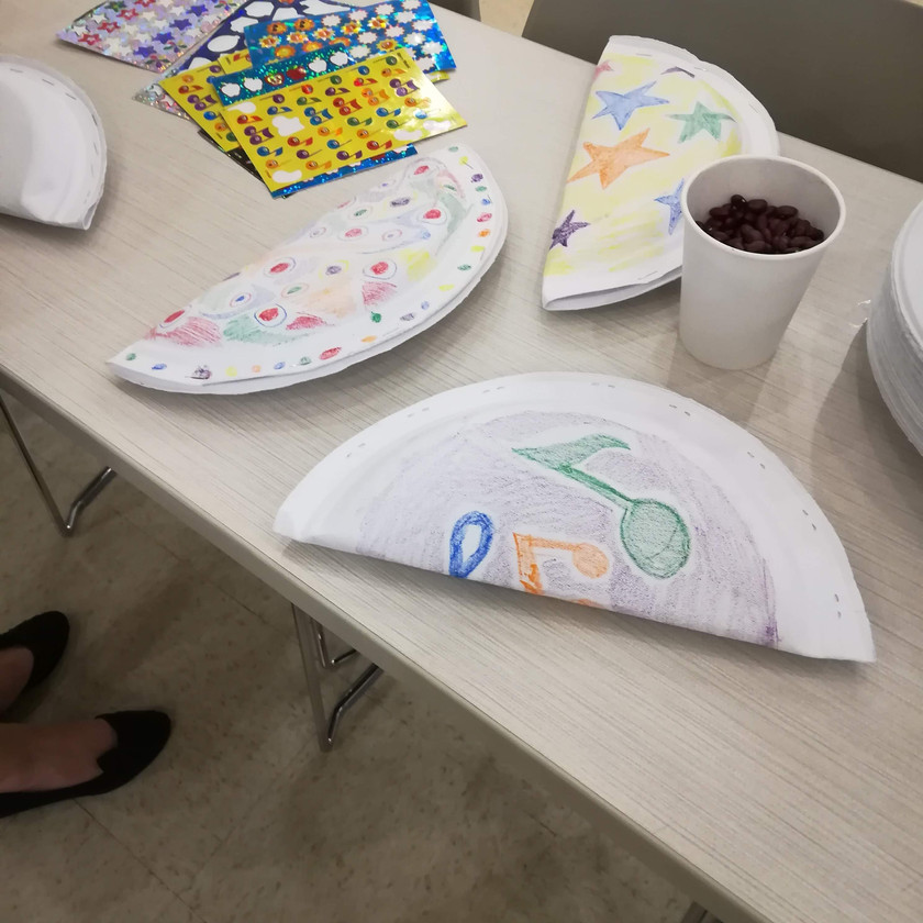"3 paper plates folded and stapled together next to paper cup with dried beans. Plate ""tambourines"" decorated with crayon stars, dots, and music notes."