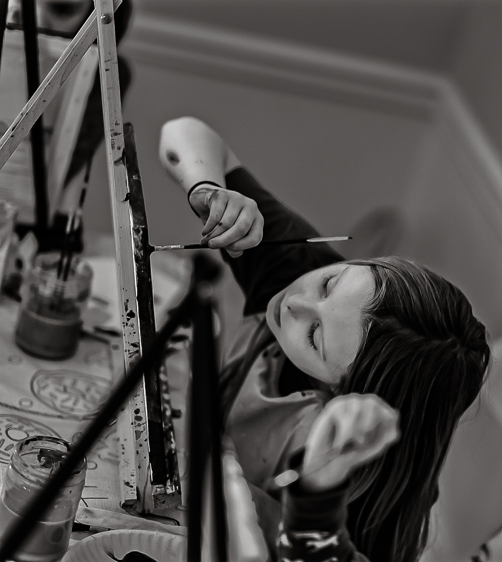 black and white photo of girl painting on canvas with acrylics